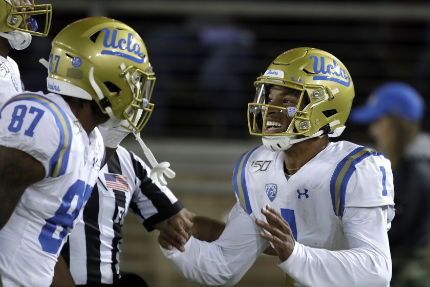 UCLA quarterback Dorian Thompson-Robinson, right, celebrates with Jordan Wilson (87) after scoring a touchdown against Stanford during the first half on Thursday in Palo Alto.