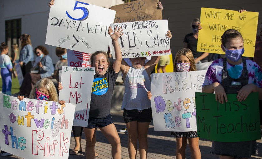 Students hold signs at a rally at the Huntington Beach City School District headquarters on Tuesday.