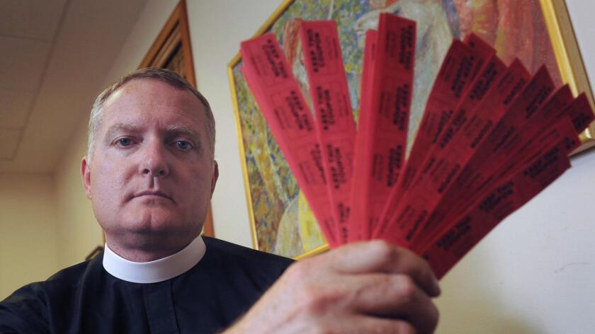 Jeremy Lucas, de la Iglesia de Cristo de Lake Oswego, muestra los 150 boletos de la rifa que compró para ganar un rifle AR-15 (Vern Uyetake/Lake Oswego Review).