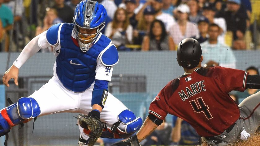Arizona's Ketel Marte beats the throw to Yasmani Grandal the Los Angeles Dodgers to score a run on a double by Adam Rosales of the Arizona Diamondbacks in the seventh inning of the game at Dodger Stadium on September 6, 2017 in Los Angeles.