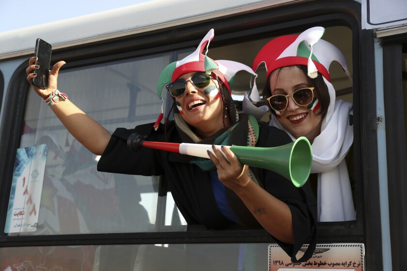 Iranian women cheer as they arrive to the Azadi Stadium
