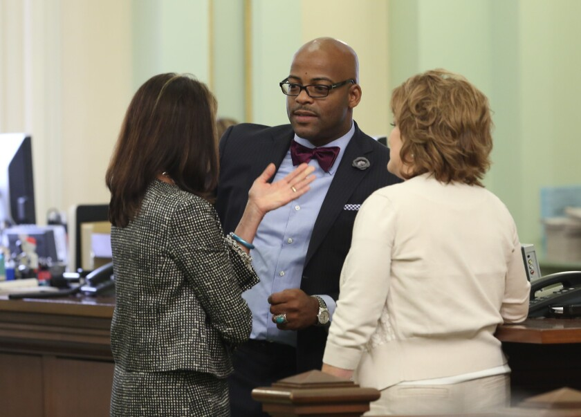 Then Assemblyman Isadore Hall III (D-Compton), center, speaks with GOP Assembly members Diane Harkey of Dana Point, left, and Shannon Grove of Bakersfield on the Assembly floor in April 2014.