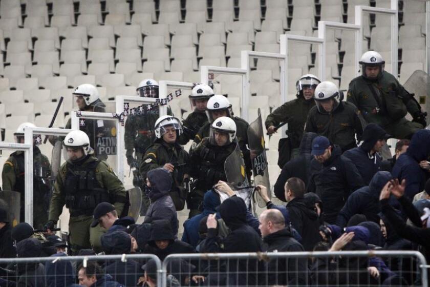 Policías griegos tratan de controlar a aficionados de Ajax, en un partido de la Liga de Campeones entre AEK y Ajax en el estadio OAKA en Atenas (Grecia). EFE