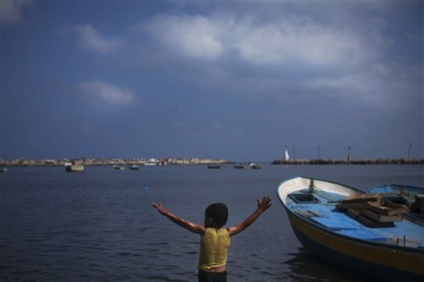 A Palestinian boy plays in the water at the port in Gaza City, Wednesday, July 14, 2010. A Libyan charity's aid ship, flanked by Israeli missile boats, was sailing in the direction of an Egyptian port on Wednesday, apparently deciding not to defy Israel's naval blockade of the Hamas-ruled Gaza Stri