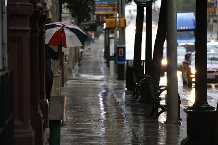 A pedestrian holds an umbrella in downtown San Antonio, Texas Tuesday Sept. 7, 2010 as Tropical Storm Hermine dumps rains in the area. Numerous Central Texas counties remain under a flash flood watch until midnight Tuesday according to the National Weather Service. Two to 5 inches of rain are expected to fall in the area. (AP Photo/San Antonio Express-News, Jerry Lara) MAGS OUT; TV OUT; NO SALES; SAN ANTONIO OUT; AP MEMBERS ONLY; MANDATORY CREDIT