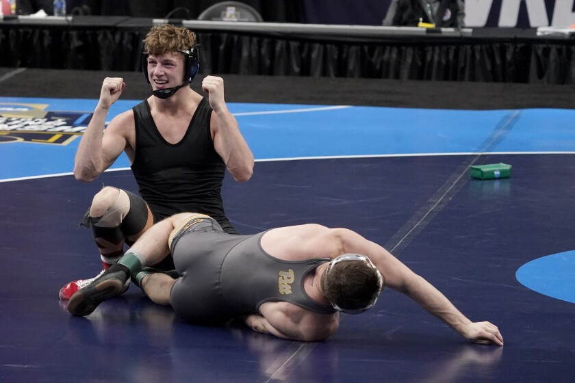 FILE - Stanford's Shane Griffith celebrates after defeating Pittsburgh's Jake Wentzel during their 165-pound match in the finals of the NCAA wrestling championships in St. Louis, in this Saturday, March 20, 2021, file photo. Griffith wore a black singlet minus the Stanford logo as a statement after the school announced in July that wrestling and 10 other sports, most of them that produce athletes for the U.S. Olympic team, would be dropped to save money. (AP Photo/Jeff Roberson, File)