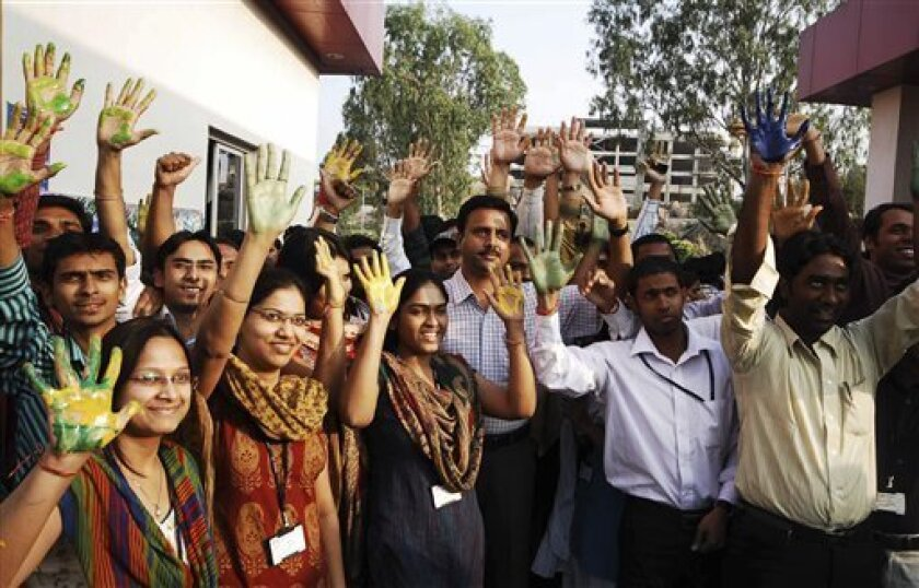 Satyam Computer Services Ltd employees reacts as they prepare to stamp their palm marks in different colors on a large poster, unseen, to express support to the company in Hyderabad, India, Thursday, Jan. 8, 2009. Top executives of the beleaguered Indian outsourcing company Satyam Computer Services
