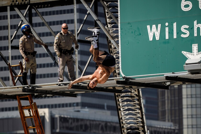 California Highway Patrol officers watch as a man who had scaled a freeway sign and shut down the southbound 110 Freeway does a backflip onto massive inflatable cushions set up below in downtown Los Angeles.