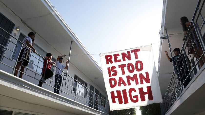 Organizers with Housing Long Beach, a local advocacy group pushing for rent control and eviction protections, hangs up a sign in the courtyard of the apartment complex on Cedar Ave. in mid-June.