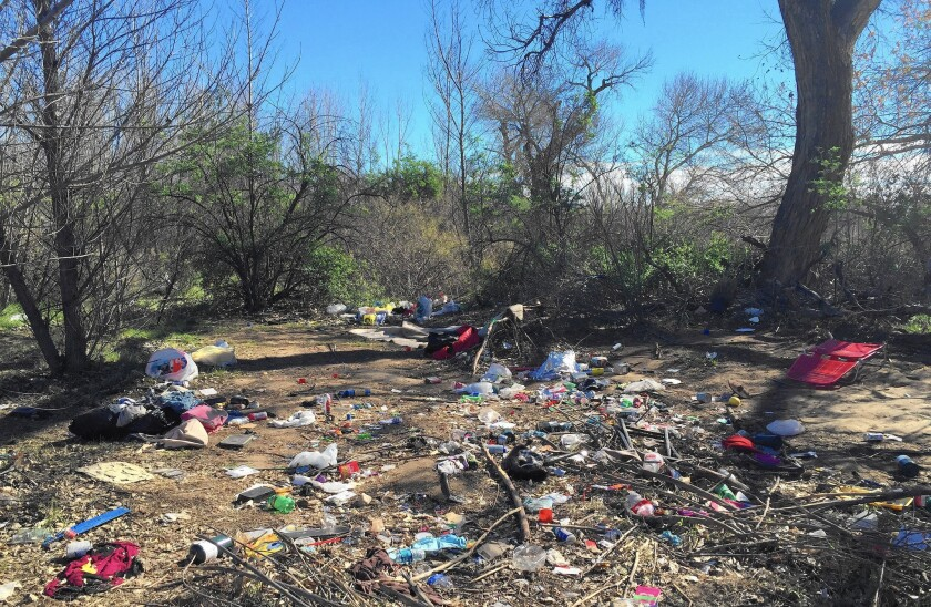 Trash and debris left by transients living in hidden encampments is strewn about the brush along the Santa Clara River bed in Santa Clarita.