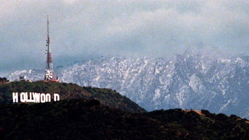 Snow forms a backdrop to the Hollywood sign after an El Niño storm in 1998.