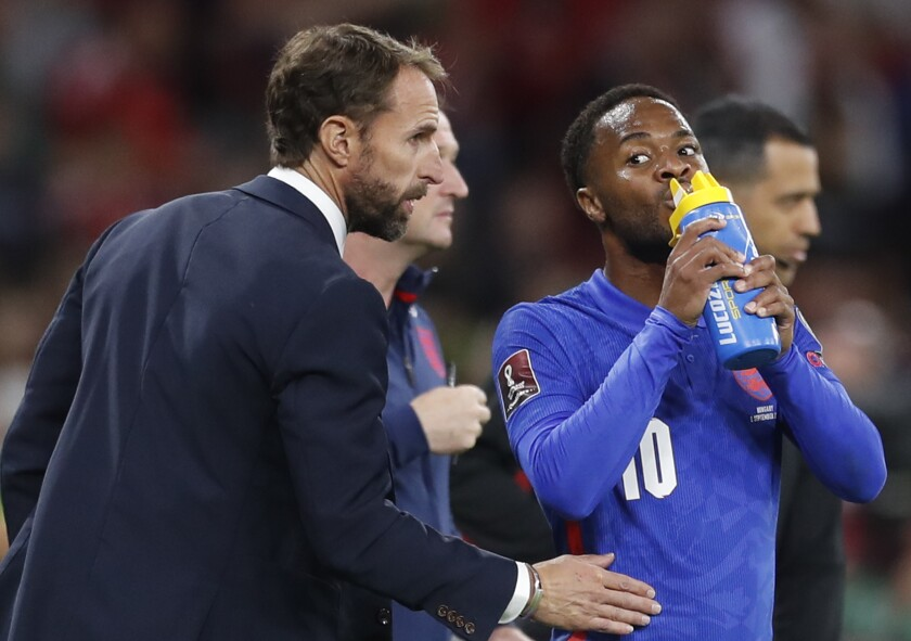 England's manager Gareth Southgate talks to Raheem Sterling during the World Cup 2022 group I qualifying soccer match between Hungary and England at the Ferenc Puskas stadium in Budapest, Hungary, Thursday, Sept. 2, 2021. (AP Photo/Laszlo Balogh)