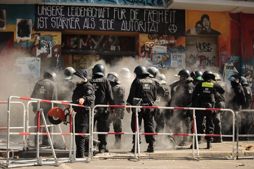Police officers open the entrance door to the house 'Rigaer 94' at the Rigaer Straße (Riga Street) in Berlin, Germany, Thursday, June 18, 2021. Police forced their way into a Berlin squat on Thursday to enable a fire safety inspection that the building's residents have been resisting, following clashes the previous day in which police say 60 officers were hurt. Slogan on top of the entrance reads: 'Our pasion for freedom is stronger than any authority'. (Carsten Koall/dpa via AP)