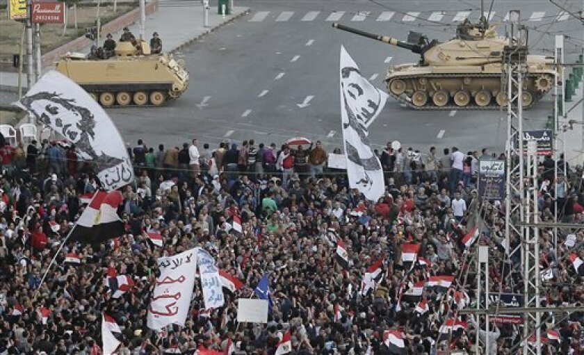 Egyptian army tanks, center, secure the perimeter of the presidential palace while protesters gather, chanting anti president Mohammed Morsi slogans, in Cairo, Egypt, Friday, Dec. 7, 2012. Egypt's political crisis spiraled deeper into bitterness and recrimination Friday as thousands of Islamist backers of the president vowed vengeance at a funeral for men killed in bloody clashes earlier this week and large crowds of the president's opponents marched on his palace to increase pressure after he rejected their demands. (AP Photo/Hassan Ammar)