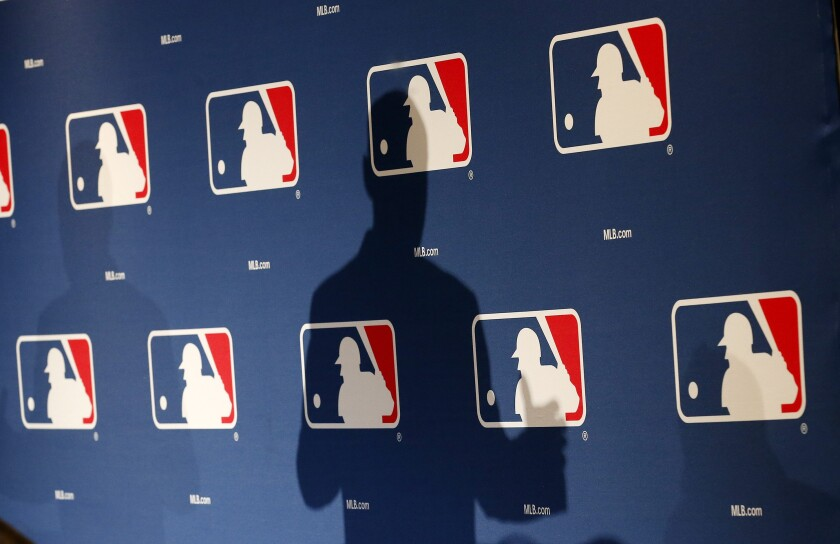 In this Feb. 23, 2015, photo, the shadow of MLB Commissioner Rob Manfred is projected on an MLB logo backdrop in Phoenix.