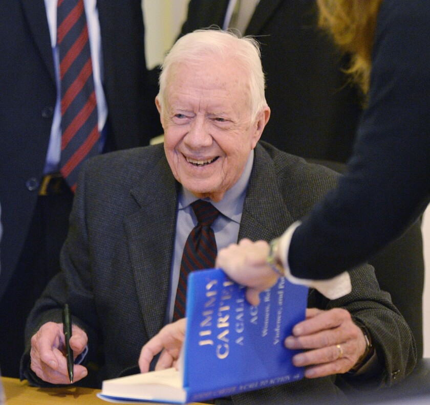 """Former President Carter signs a copy of his new book, """"A Call to Action: Women, Religion, Violence, and Power,"""" at a Chicago bookstore. At a stop in Portland, Ore., he signed 1,600 copies in one sitting"""