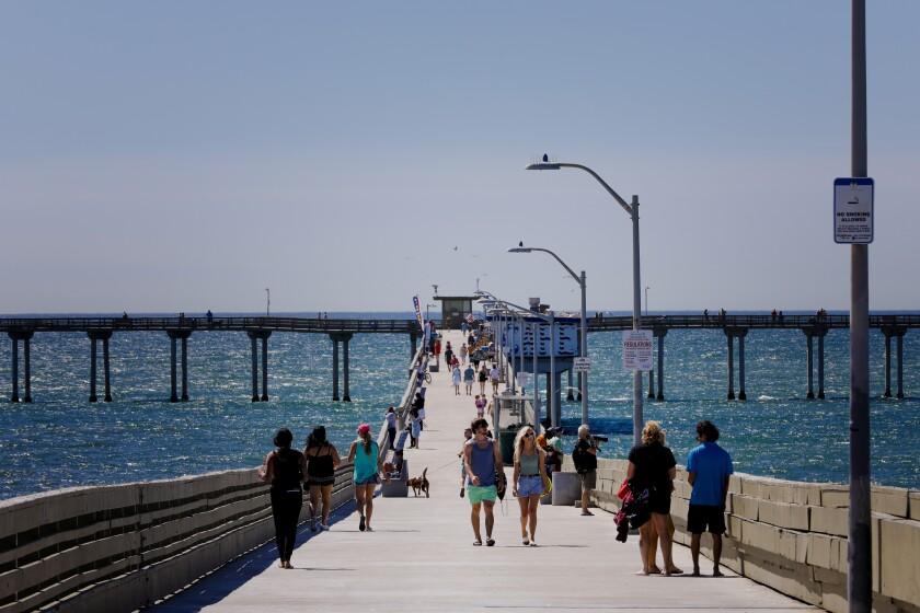Visitors walk on the Ocean Beach Pier in June.