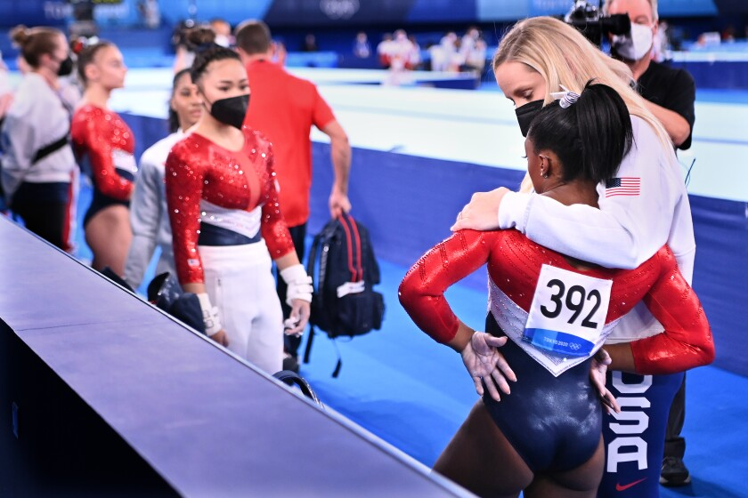 A woman stands with her arm around Simone Biles at the Tokyo Olympics.