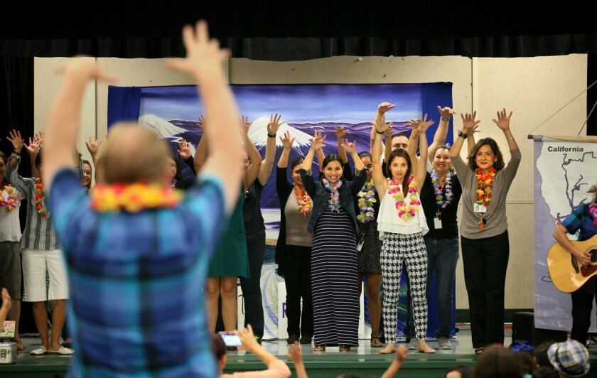 Tuba Heatherton leads teachers in a hula during a Shows That Teach water education assembly at the Nestor Language Academy Charter School.