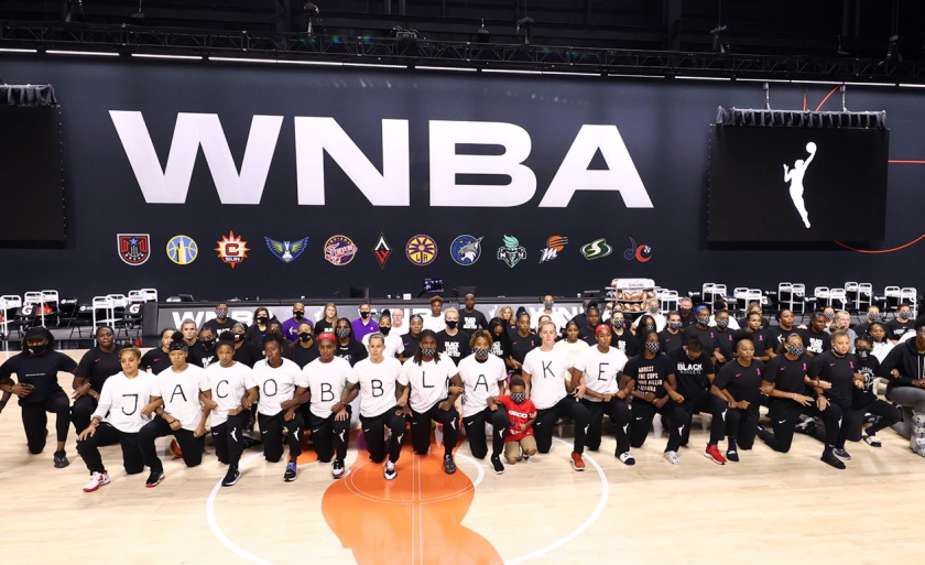Members of four WNBA teams lock arms on court on Wednesday, the first day of the league's stoppage.