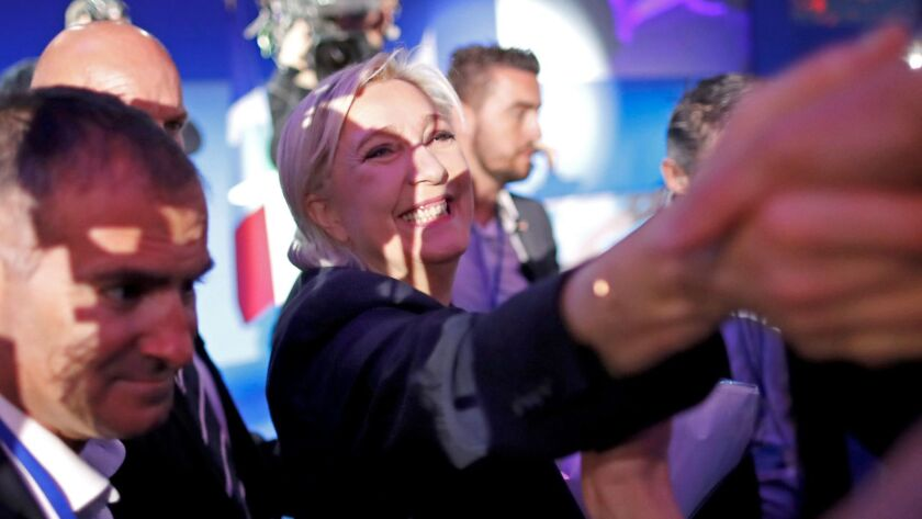 French presidential candidate Marine Le Pen is greeted by supporters after finishing second in the f