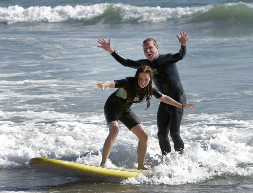 A tandem ride is a blast for Chris Erskine and his younger daughter at surfing school in Santa Monica.