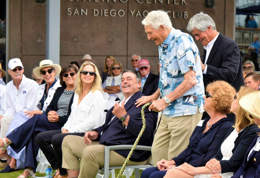 """Charles """"Kim"""" Fletcher, with his cane, got a thumb's up from America's Cup winner Dennis Conner, seated to his right, as he walked up to give his talk at the celebration of life for Lowell North at the San Diego Yacht Club on June 22. Standing behind him is U.S. National Sailing Hall of Fame member Vince Brun."""