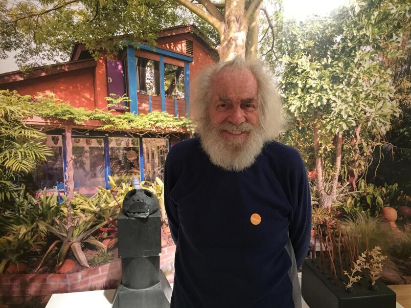 Erik Gronborg poses in front of a full-scale photo of his garden as part of the exhibit, 'The Erik Gronborg Experience' — on view through March 12, 2017 at Mingei International Museum, 1439 El Prado in Balboa Park, San Diego.