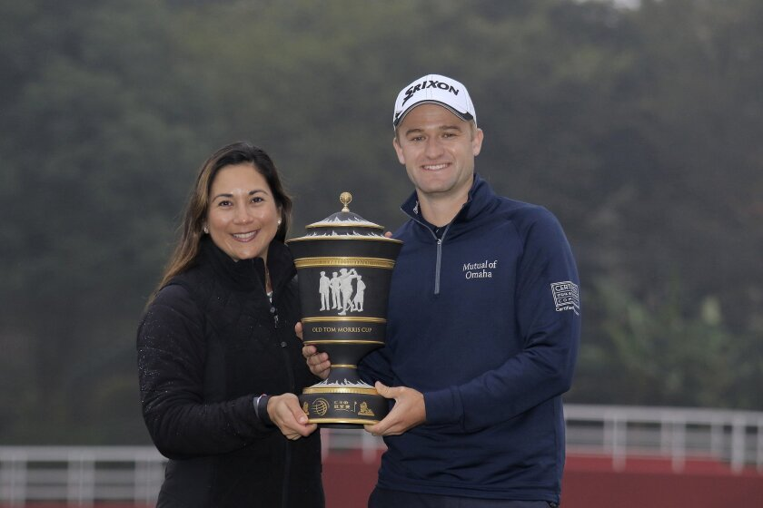 Russell Knox of Scotland and his wife Andrea Knox pose with his champion trophy during the award ceremony of the HSBC Champions golf tournament at the Sheshan International Golf Club in Shanghai, China Sunday, Nov. 8, 2015. (AP Photo)