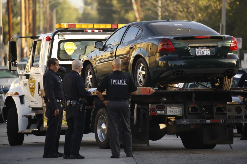 LAPD gang detectives watch as a bullet-riddled car is taken away after a woman was shot in the Hyde Park neighborhood of South L.A. early Wednesday morning.