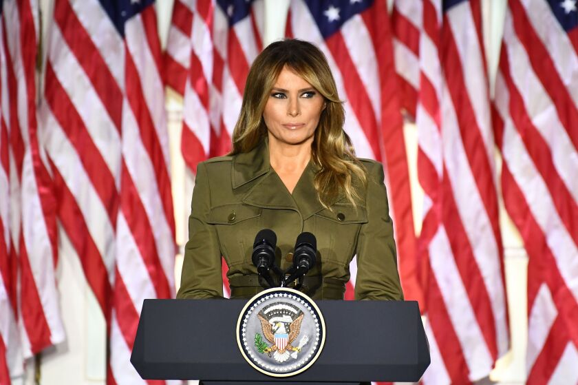 Melania Trump addresses the Republican convention from a podium outside the White House; American flags hang behind her.