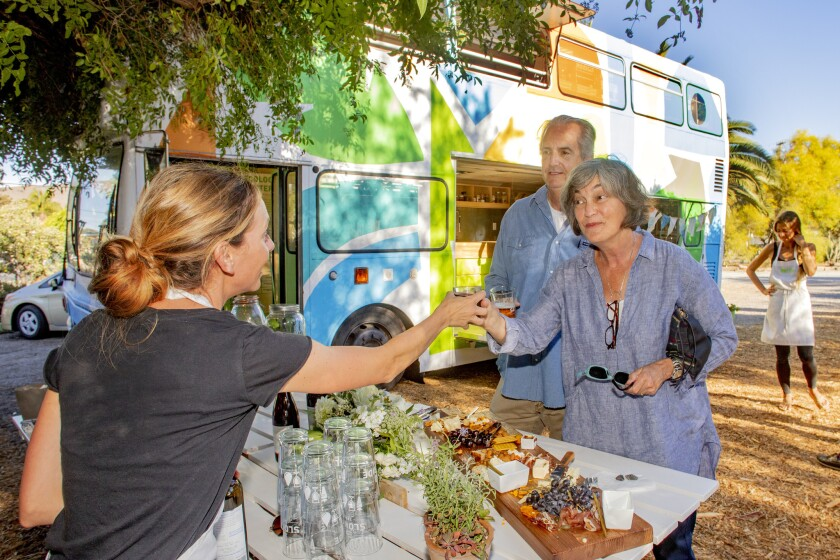 Michelle Rais serves a beverage to Greg and Sally Garrett in front of the Ecology Center's 32-foot-long double-decker bus called Road Trip, which serves as a mobile ecology workshop.