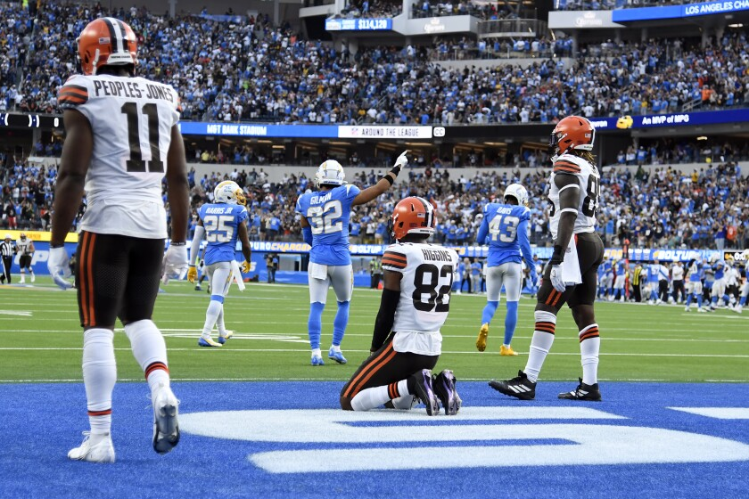 Cleveland Browns player kneel and stand in the end zone after a failed Hail Mary pass to end an NFL football game against the Los Angeles Chargers Sunday, Oct. 10, 2021, in Inglewood, Calif. (AP Photo/Kevork Djansezian)