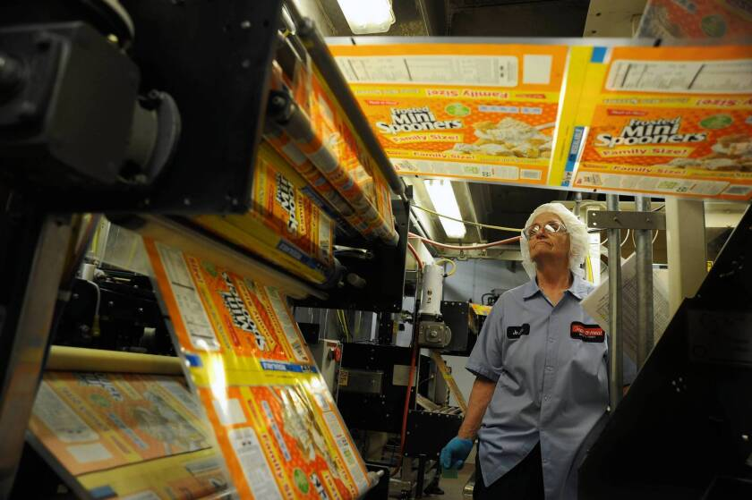 Joann Flicek watches a bagging machine for Frosted Mini Spooners at MOM Brands.