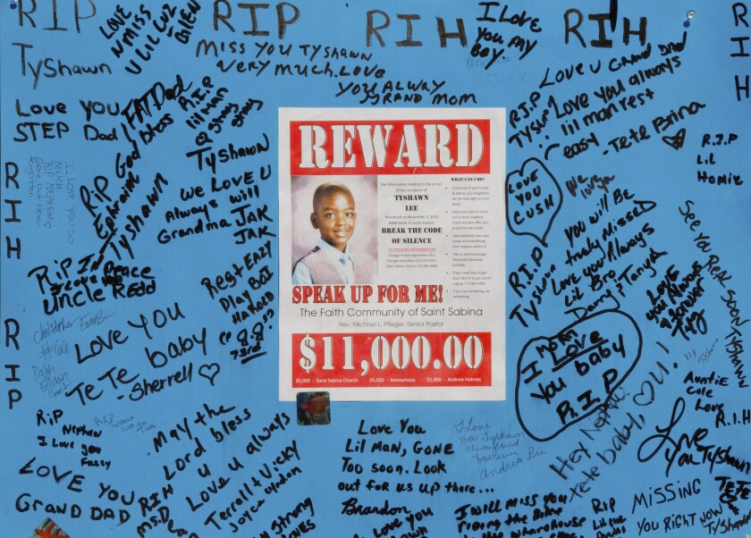"""FILE - In this Nov. 4, 2015, file photo, a reward sign and messages hang near the site where Tyshawn Lee was fatally shot in Chicago. The trial of two men charged with first-degree murder in the 2015 slaying of the 9-year-old Chicago boy got underway Tuesday, Sept. 17, 2019, with a prosecutor noting the victim brought a basketball to a park while his alleged killers """"brought guns."""" (AP Photo/Teresa Crawford, File)"""