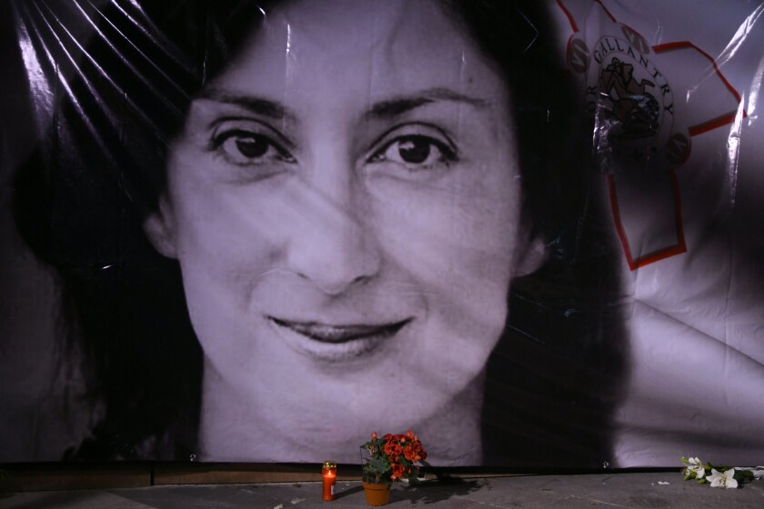 FILE - In this Tuesday, Oct. 16, 2018 file photo, flowers and a candle lie in front of a portrait of slain investigative journalist Daphne Caruana Galizia during a vigil outside the law courts in Valletta, Malta. One of three men accused of killing Maltese investigative journalist Daphne Caruana Galizia in a 2017 car bombing changed his plea to guilty during a hearing Tuesday and was immediately sentenced to 15 years in prison. The man, Vince Muscat, together with Alfred and George Degiorgio, had been accused of detonating the bomb that killed Caruana Galizia as she was driving her car Oct. 16, 2017. (AP Photo/Jonathan Borg, File)