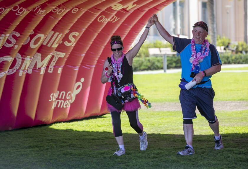 Tracy and Michael David raise their arms to celebrate as they make their way to the finish line at Waterfront Park in San Diego after taking part in the Susan G. Komen 3-Day walk on Sunday. The 3 day, 60-mile walk for women and men who want to make a personal difference in the fight against breast cancer.