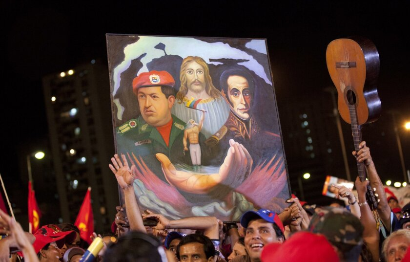FILE - In this April 11, 2013 file photo, supporters attend the closing campaign rally for Venezuela's acting President Nicolas Maduro, where they hold up a painting depicting late President Hugo Chavez, left, Jesus Christ, center, and independence hero Simon Bolivar, right, in Caracas, Venezuela. Chavez's legacy has taken on a religious glow in Venezuela since the leader's death. Chavez shrines, rosaries adorned with his face and images depicting him with a Christian cross have become commonplace. Followers often say they believe Chavez was on a divine mission. (AP Photo/Ramon Espinosa, File)