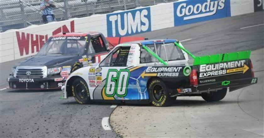 Dusty Davis, left, avoids J.R. Fitzpatrick, as he spins out during the NASCAR Camping World Truck Series auto race, Saturday, March 31, 2012. (AP Photo/Don Petersen)