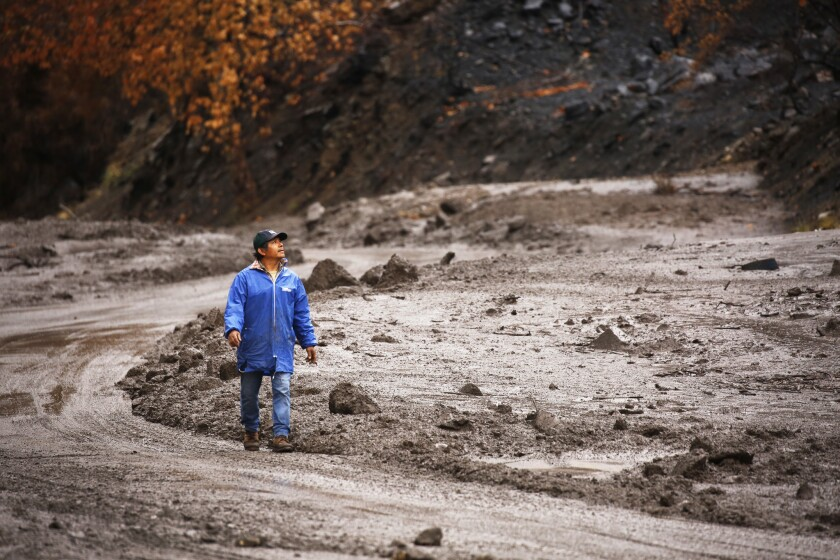 Mario Romero looks at mud debris covering Maricopa Highway 33 north of Ojai, which has several closures due to mud and debris slides covering the roadway.