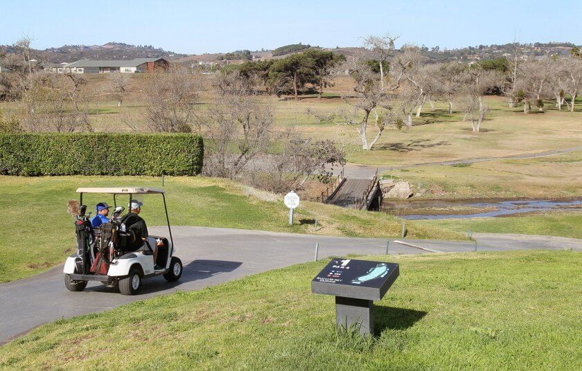 Golfers head out to the course at the San Luis Rey Downs Country Club last year before it closed in August.