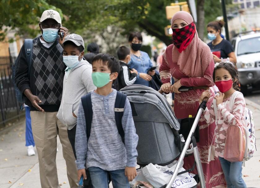 Padres acompañan a sus hijos afuera de la escuela primaria PS 179 en el vecindario de Kensington