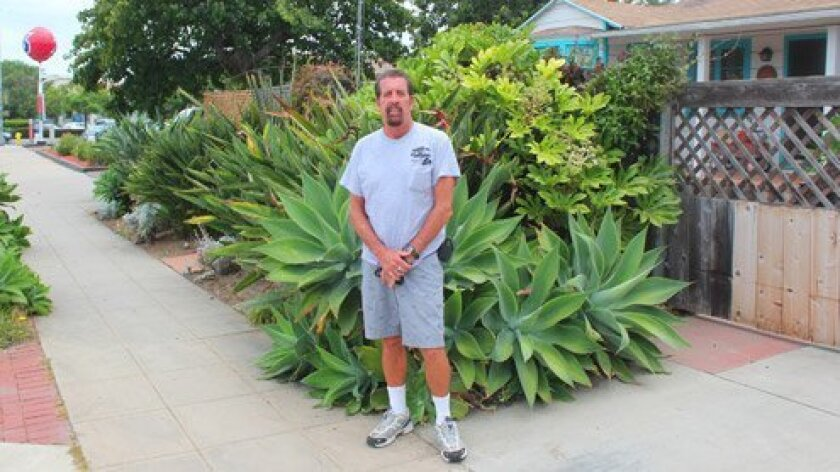 La Jolla business owner and resident Doug Moranville stands near his Eads Avenue home, adjacent the Unocal gas station on Pearl Street. The property owner wants to remove the station and add a mix of condos, retail and restaurant space. Moranville and his wife, Karen, oppose the size and density of