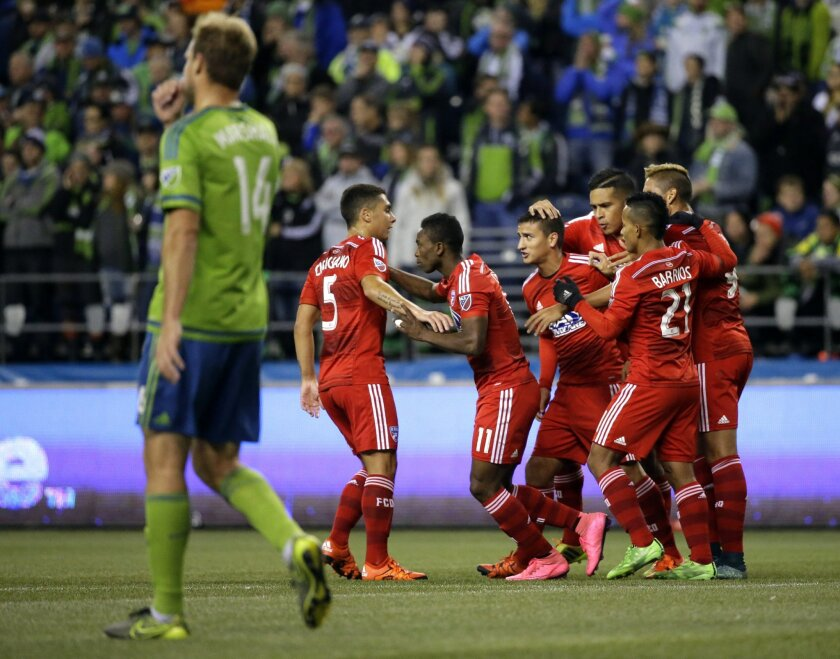 Seattle Sounders' Chad Marshall, left, walks to the center of the field as FC Dallas players celebrate after Dallas' Fabian Castillo, third from left, scored a goal in the first half of an MLS soccer western conference semifinal playoff match, Sunday, Nov. 1, 2015, in Seattle. (AP Photo/Ted S. Warr