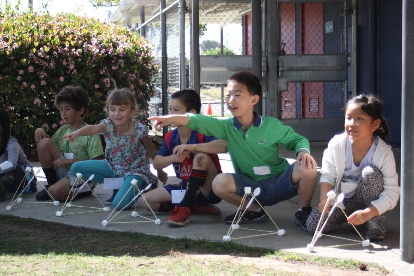 Levi Dinnenberg, Sophie Castaneda, Lance Biagioli, Hansong Cao and Sehee Sim observe how far their jellybeans went after being propelled from the launchers they made.