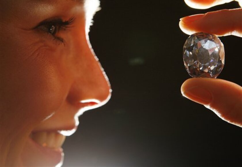 Becky Markley holds the Wittelbach diamond, a rare 35.6 carat 17th century grey-blue diamond, at Christie's auction house in London, Friday, Dec. 5, 2008. The diamond was part of the dowry of the Infanta Mararita Teresa upon her engagement to Leopold I of Austria, given by her father King Philip IV of Spain, and is expected to sell for some 9 million pounds, ($ 15 million, euro 10.4 million ), at auction on Dec. 10. (AP Photo/Alastair Grant)
