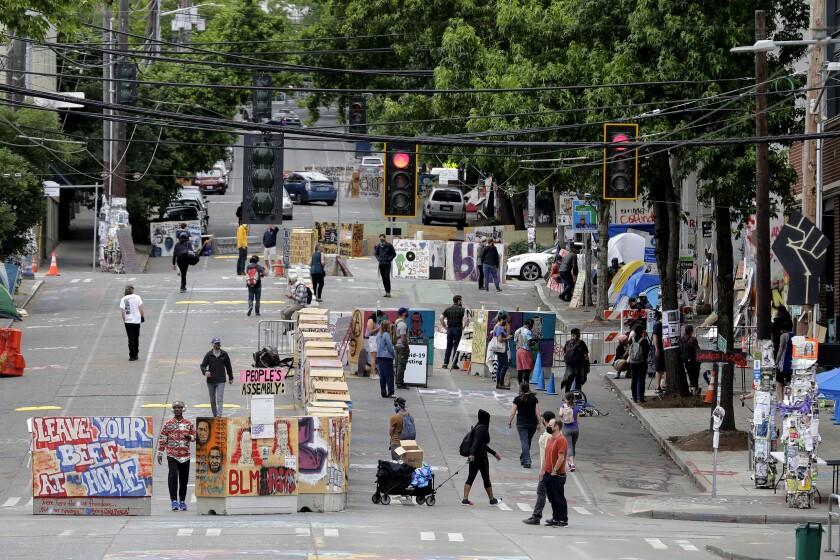 Occupiers, residents and visitors walk by barricades Wednesday in Seattle's Capitol Hill Occupied Protest zone.