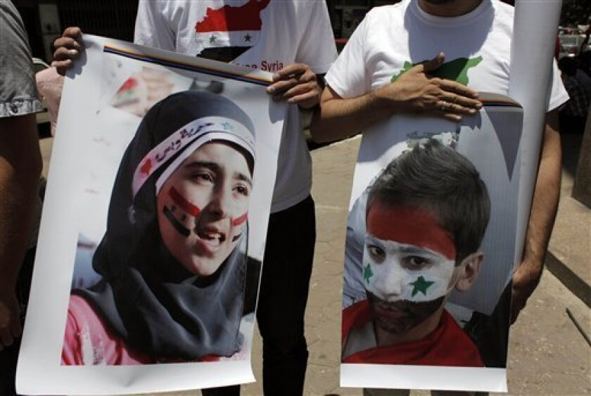 Two protesters carry posters with pictures of unidentified relatives in Syria, with the Syrian flag colors painted on their faces during an anti-Syrian regime rally near the Syrian embassy in Cairo, Egypt Tuesday, July 5, 2011. Syrian troops fired Tuesday on residents who set up makeshift roadblocks to prevent the advance of tanks ringing the city of Hama, which has become a flashpoint of the uprising against autocratic President Bashar Assad, activists said. (AP Photo/Nasser Nasser)