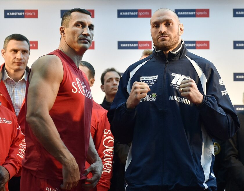 Challenger Tyson Fury, right, and world champion Wladimir Klitschko, left, stand on the podium after the Official Weigh-In in Essen, Germany, prior their heavyweight boxing fight, Friday, Nov. 27, 2015. The title clash will take place in Duesseldorf's LTU arena on Saturday. (AP Photo/Martin Meissner)