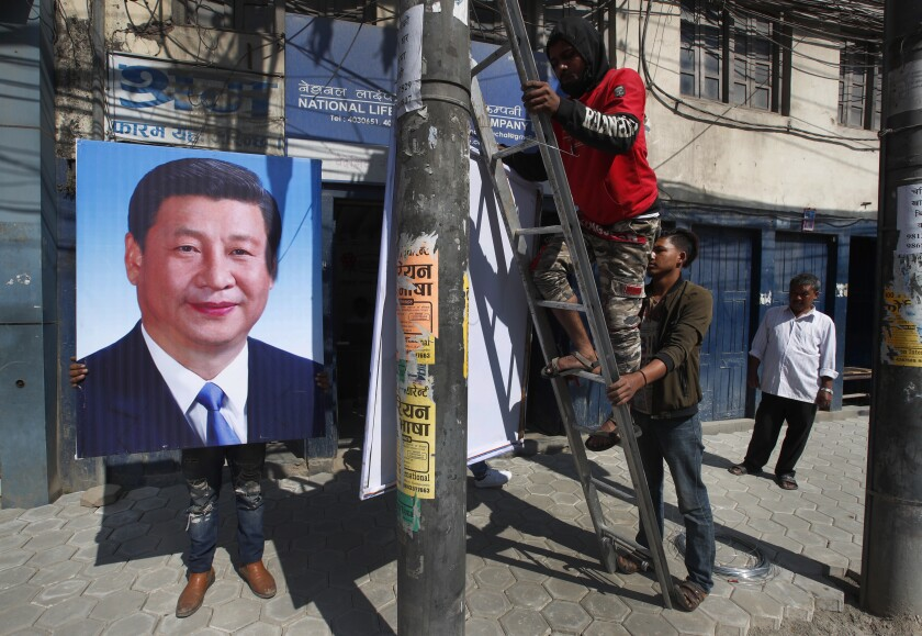 Nepalese workers work to hang portraits of Chinese president Xi Jinping in Kathmandu, Nepal, Friday, Oct. 11, 2019. Officials from both China and Nepal have confirmed that Xi will be arriving in Kathmandu on Saturday. It will the first visit of a Chinese president in 23 years since Jiang Zemin visited in 1996. (AP Photo/Niranjan Shrestha)